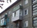 Застекленный балкон с раздвижными створками и отделка парапета сайдингом